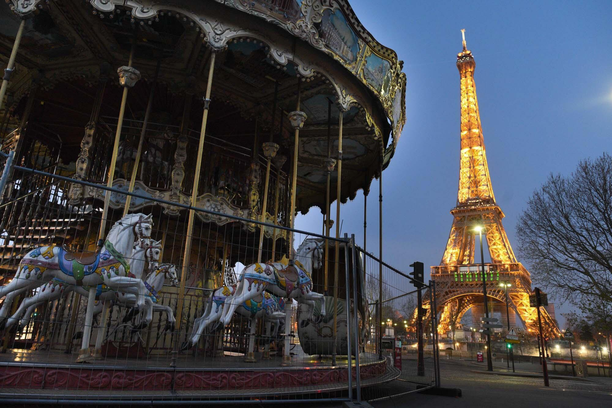 An empty merry-go-round near the Eiffel Tower. All non-essential commercial activities have been banned until at least April 15.