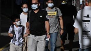 Des piétons portent un masque de protection dans une rue de Hong Kong, le 27 juillet 2020