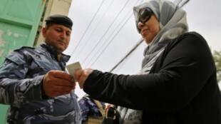 رجل أمن يتحقق من هوية عراقية في مركز اقتراع في حي الكرادة في بغداد في 12 ايار/مايو 2018