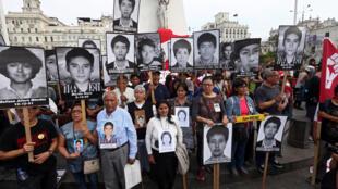 Personas sostienen retratos de algunas de las víctimas del conflicto de los 80 y 90 después de que el presidente peruano Pedro Pablo Kuczynski perdonara al expresidente Alberto Fujimori en Lima, Perú, el 25 de diciembre de 2017.