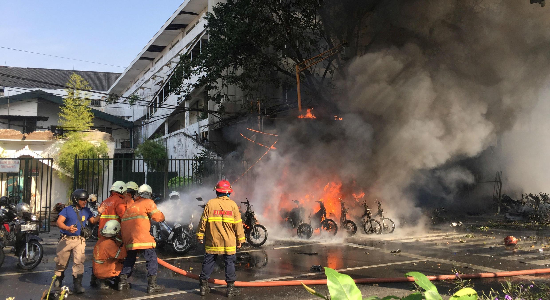 Los bomberos apagan el fuego después del atentado contra una inglesia pentecostal en Surabaya, Indonesia. 13/5/18