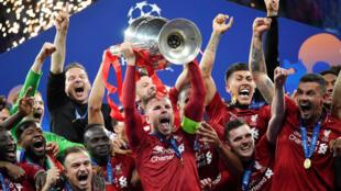 Jordan Henderson, del equipo Liverpool, levanta el trofeo mientras celebran después de ganar la Liga de Campeones contra el Tottenham en Madrid, España, el 1 de junio de 2019.