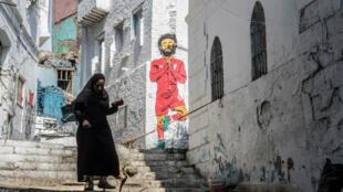 Une femme égyptienne passe devant une peinture murale de la star des Pharaons Mohamed Salah au Caire, le 17juin2019.