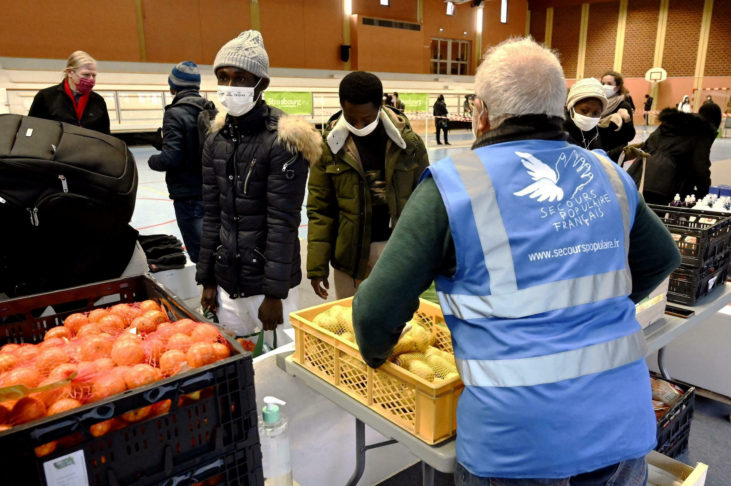 Students queue to receive a food aid package during a distribution by French charity 'Secours Populaire' in Strasbourg, eastern France, on December 12, 2020.