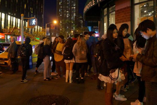 Des lycéens déguisés pour Halloween sont rassemblés à l'extérieur d'un restaurant, dans le quartier de Manhattan où a eu lieu l'attentat.