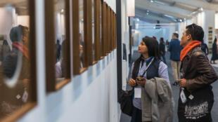 """Personas mirando la instalación """"High Res"""" dentro de la Feria de Arte India, Nueva Delhi, India, el 9 de febrero de 2018"""