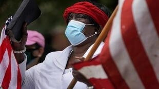 A woman holds an American flag and a Bible outside the funeral for Rayshard Brooks, the Black man shot dead by an Atlanta police officer, at Ebenezer Baptist Church in Atlanta, Georgia, US on June 23, 2020.