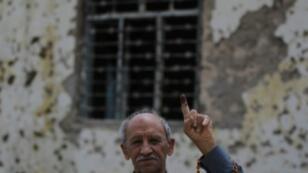 Un hombre muestra su dedo con tinta, símbolo del ejercicio del voto, durante las elecciones parlamentarias del sábado 12 de mayo de 2018, cuya participación ha sido la más baja desde la invasión estadounidense.