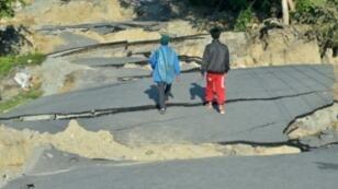رجلان يسيران على طريق في مدينة بالو بجزيرة سولاويسي في 1 أكتوبر 2018.