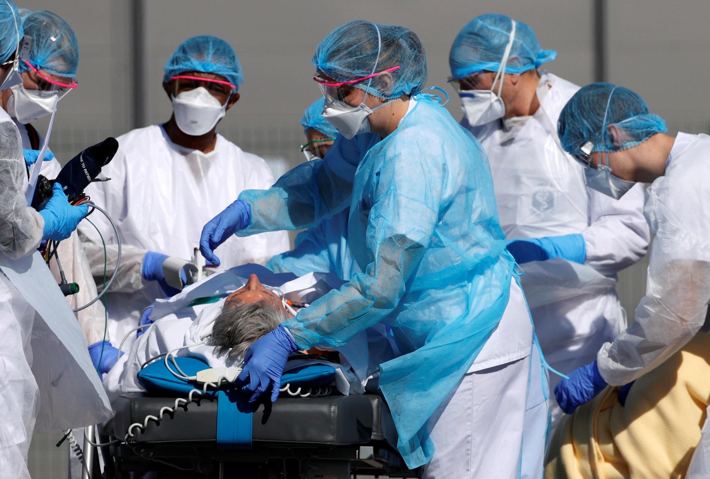 طاقم طبي يسعف أحد المصابين بفيروس كورونا