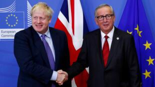 El presidente de la Comisión Europea, Jean-Claude Juncker, y el primer ministro británico, Boris Johnson, se estrechan las manos durante una conferencia de prensa después de llegar a un acuerdo sobre el Brexit, al margen de la cumbre de líderes de la Unión Europea, en Bruselas, Bélgica, el 17 de octubre de 2019.