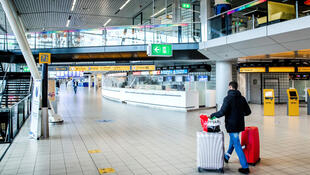 "A traveler walks in a deserted Schipol airport in Amsterdam on January 13, 2021, amid the Covid-19 pandemic. A Dutch police spokesman confirmed that ""a suspect who figured on Europol's list of the most wanted persons"" was arrested on Friday morning after landing at the airport."