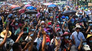 Des manifestants font le salut à trois doigts lors d'un rassemblement à Rangoun, le 2 mars 2021 en Birmanie
