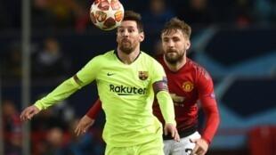 L'attaquant et capitaine du FC Barcelone Lionel Messi (c) aux prises avec le défenseur de Manchester United Luke Shaw (d) en quart de finale aller de la Ligue des champions, le 10 avril 2019 à Manchester