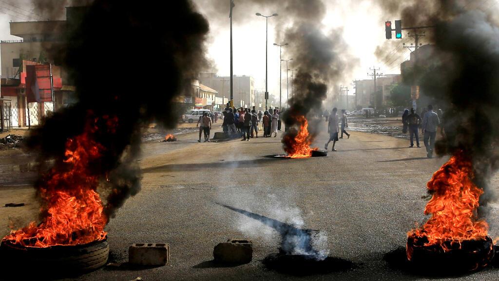 Los manifestantes utilizan neumáticos quemados para erigir una barricada en una calle, exigiendo que el Consejo Militar Transicional entregue el poder a los civiles, en Jartum, Sudán, el 3 de junio de 2019.