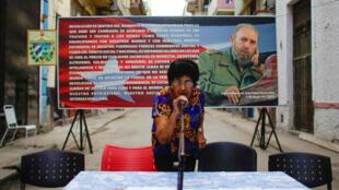 Un miembro de una comisión electoral prueba un micrófono al frente de una imágen de Fidel Castro en La Habana. 4 de septiembre 2017.