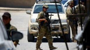 جندي أمريكي يؤمن الحراسة خلال أحد الاجتماعات الأمنية بمدينة الطبقة قرب الرقة في 29 حزيران/يونيو 2017