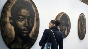 """Une visiteuse regarde une oeuvre de l'artiste Alexis Peskine à la foire d'art contemporain """"Also known as Africa"""" (AKAA), le 8 novembre 2018 à Paris."""