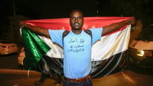 """Un sudanés se manifiesta con una bandera nacional con una escritura en el pecho en árabe que lee """"Revolucionarios libres"""", durante una manifestación contra el nuevo consejo militar gobernante establecido después de la destitución del presidente Omar al-Bashir, en Jartum, Sudán, el 11 de abril de 2019."""