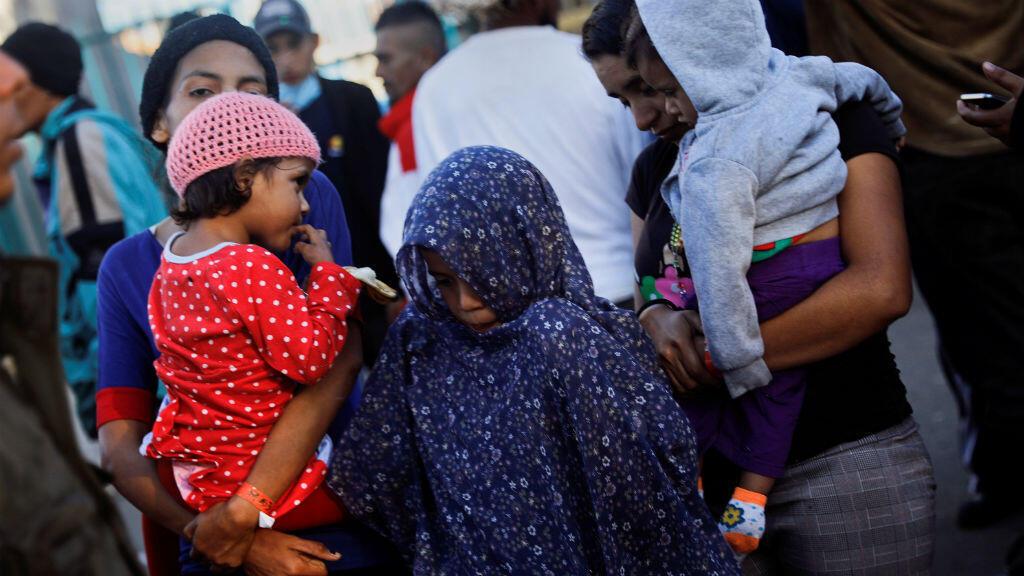 Migrantes de Centroamérica que intentan llegar a Estados Unidos, hacen fila para buscar comida afuera de un refugio temporal en Tijuana, México, el 22 de noviembre de 2018.