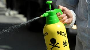 """Un manifestante usa un aerosol durante una protesta llamada """"Marcha contra Monsanto"""" en Hamburgo, Alemania, el 18 de mayo de 2019."""