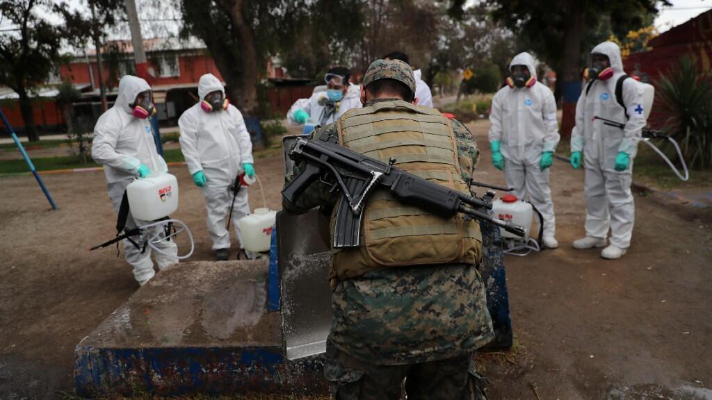 Varios militares aguardan para desinfectar los productos usados por uno de sus compañeros en Maipú, dentro del área metropolitana de Santiago de Chile, en Chile. 16 de junio de 2020.