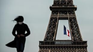 امرأة ترتدي قناعاً واقياً أمام برج إيفل في باريس في 11 أيار/مايو 2020