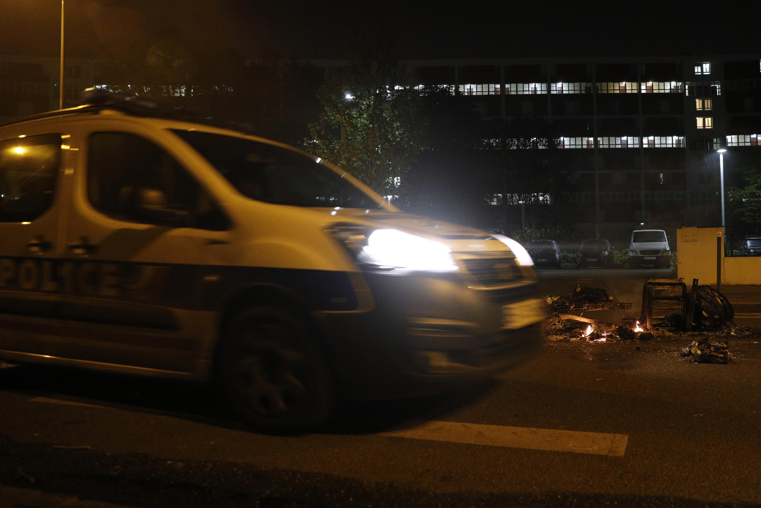 """A French police vehicle drives past a pile of burning trash in front of the """"Les Jardins de la Noue"""" apartment building in Villeneuve-la-Garenne, in the northern suburbs of Paris, early on April 20, 2020."""