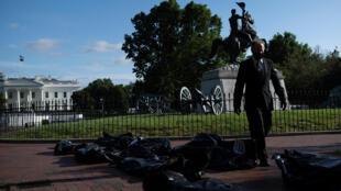 ناشط يسير وسط أكياس تستخدم للفّ الجثث وضعت أمام البيت الأبيض في واشنطن احتجاجاً على طريقة تعامل إدارة الرئيس دونالد ترامب مع أزمة كوفيد-19 في 20 ايار/مايو 2020.