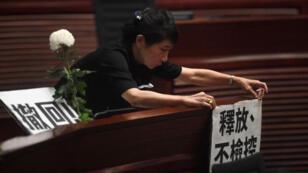 En una tensa sesión celebrada en el Parlamento de Hong Kong, la legisladora de oposición Claudia Mo sostiene un cartel con críticas sobre la forma en la que el Ejecutivo manejó la crisis.