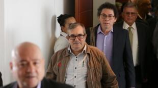 El exlíder de las FARC, Rodrigo Londoño, sale de la sala del tribunal, seguido por el excomandante guerrillero Pastor Alape, luego de comparecer ante el tribunal especial de paz de Colombia, en Bogotá, el 23 de septiembre de 2019.