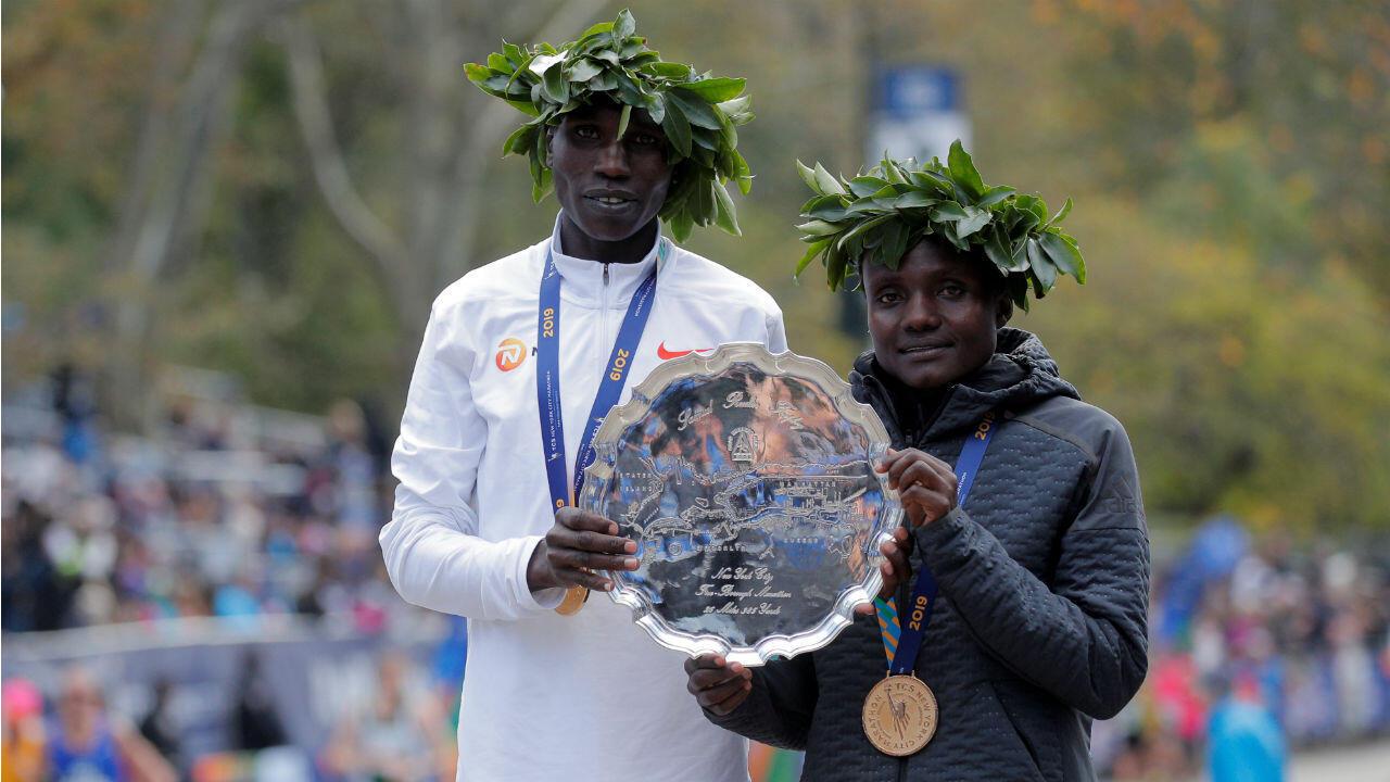 Los dos kenianos Geoffrey Kamworor de Kenia y Joyciline Jepkosgei posan con un trofeo mientras celebran ganar las carreras élites masculina y femenina.