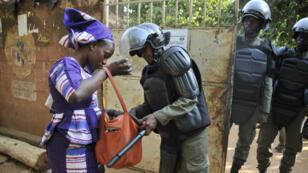 Une femme est fouillée avant d'entrer dans un bureau de vote, le 20 novembre 2016 à Bamako.