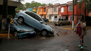 A woman walk in front of damaged cars during floods caused by Tropical Storm Amanda, in San Salvador, El Salvador May 31, 2020.