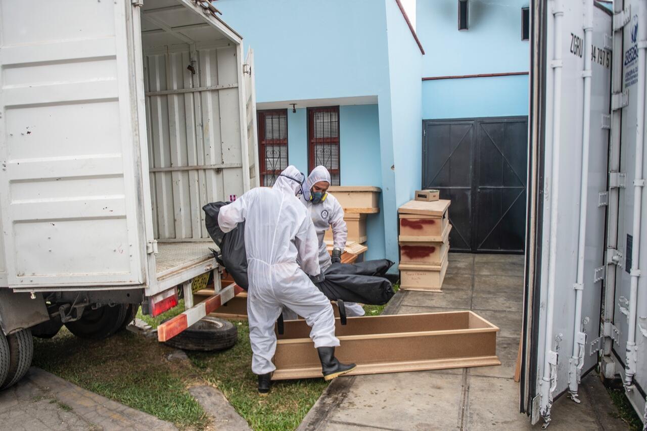 Dos empleados sanitarios trasladan en una bolsa el cuerpo de una víctima de Covid-19 fuera de un contenedor refrigerado antes de su cremación en Lima, Perú, el 21 de mayo de 2020.
