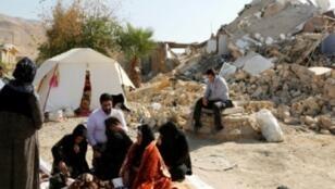 إيرانيون يجلسون أمام منازلهم المدمرة في بلدة كويك بعد الزلزال الذي ضرب غرب إيران في 15 تشرين الثاني/نوفمبر 2017