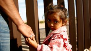 Una niña migrante, que forma parte de una caravana de miles de personas que viajan desde América Central hacia Estados Unidos, toma la mano de su padre mientras miran a través de la valla fronteriza entre México y Estados Unidos cuando se mudan a un nuevo refugio en Mexicali, México, 19 de noviembre. 2018.