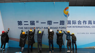 GREG BAKER / AFP | Workers take down a Belt and Road Forum panel outside the venue of the forum in Beijing, China on April 27, 2019.