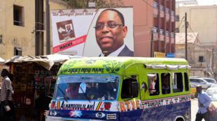 Un minibus passe devant une affiche de campagne du président sénégalais Macky Sall dans les rues de Dakar le 4 février 2019.
