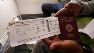Un pasajero muestra un pasaporte de Etiopía y un pase de abordar de Ethiopian Airlines mientras se encuentra dentro del vuelo a la capital de Eritrea, Asmara, desde el Aeropuerto Internacional Bole en Addis Ababa, Etiopía , el 18 de julio de 2018.