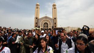 Des personnes en deuil portent le cercueil de l'un des victimes de l'attentat à Alexandrie lors d'une procession à Borg el-Arab, près d'Alexandrie, le 10 avril 2017.