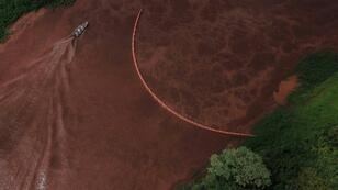 A boat sails the Paraopeba River in Brazil after the collapse of a dam at a mine belonging to Vale near Brumadinho
