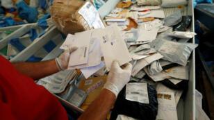 Un trabajador palestino muestra artículos enviados por correo hace ocho años cuando llegan a su destino, después de que Israel permitió el envío de cartas en Cisjordania desde Jordania, donde estaban detenidos. Jericó, Cisjordania, el 19 de agosto de 2018.