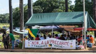 """Des manifestants guyanais ont accroché une banderole """"Non à la précarité"""" sur un barrage installé sur la route entre l'aéroport d'Eboue et Cayenne, le 29 mars 2017."""