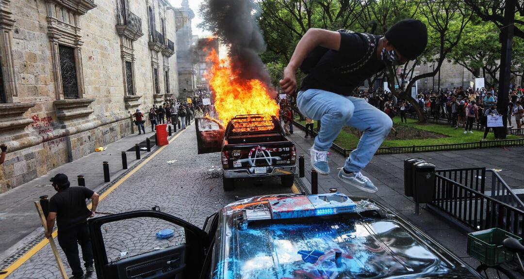 Un manifestante salta sobre un vehículo policial dañado después de que los manifestantes le prendieron fuego durante una protesta para exigir Justicia para Giovanni López. Guadalajara, México, el 4 de junio de 2020.