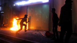 Un manifestante libanés, frente a la entrada de un banco en llamas en Saida el 29 de abril de 2020