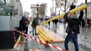 Les magasins de luxe protègent leur vitrine avec de larges panneaux de bois avant la mobilisation des Gilets jaunes.