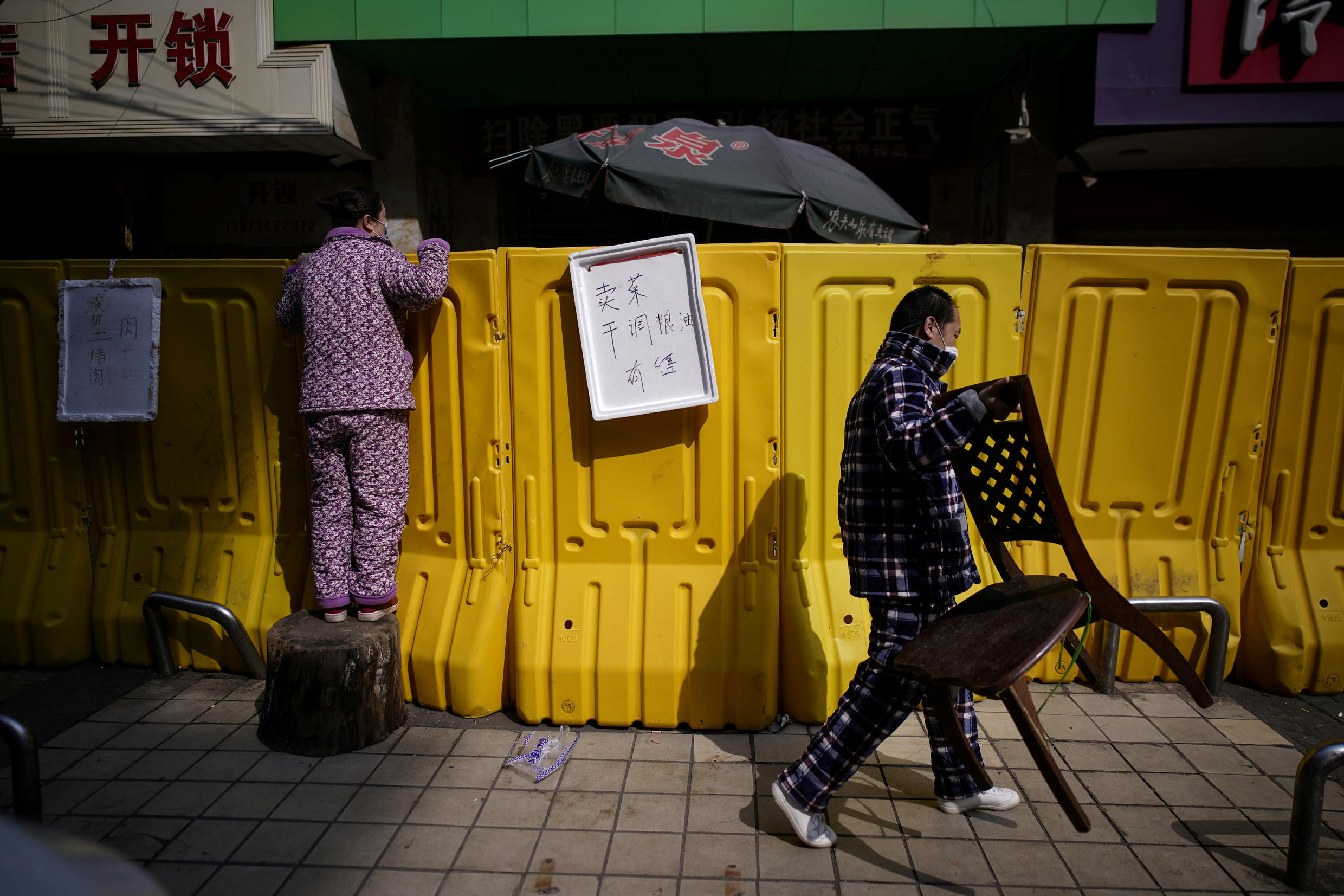 A resident pays for groceries by standing on a tree stump to peer over barriers set up to ring-fence a wet market on a street in Wuhan on April 1, 2020.