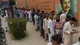 Des responsables de bureau de vote attendent de recevoir du matériel à Karachi, le 24 juillet 2018.
