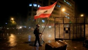 A demonstrator holds the Lebanese flag during a protest against the newly formed government outside the government headquarters in downtown Beirut, Lebanon January 25, 2020. REUTERSAli Hashisho